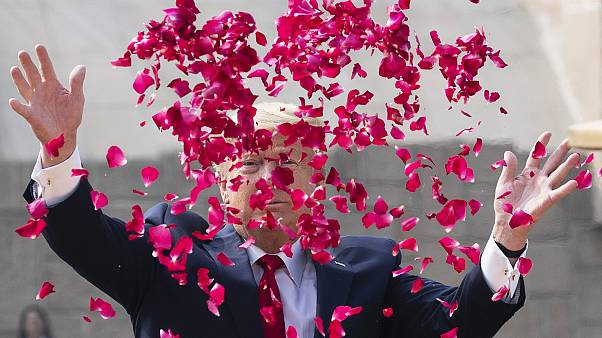 President Donald Trump throws rose petals during a ceremony at the Raj Ghat Mahatma Gandhi Memorial, in New Delhi, India.