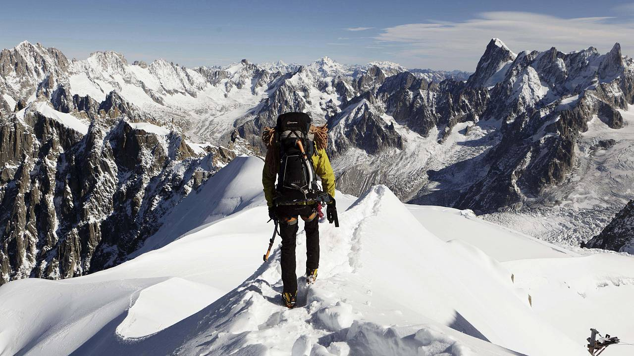 an alpinist heads down a ridge on the Aiguille du Midi towards the Vallee Blanche on the Mont Blanc massif, in the Alps, France on Oct. 12, 2011.