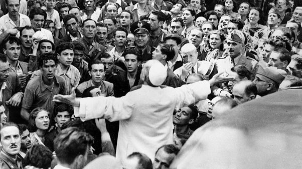 In this Oct. 15, 1943 file photo, men, women and soldiers gather around Pope Pius XII in Rome, Italy