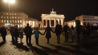 A vigil for victims of last night's shooting in Hanau is held in front of the Brandenburg Gate in Berlin, Germany, Thursday, Feb. 20, 2020.