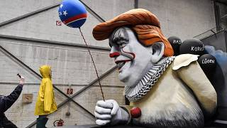 A man takes a picture of a satiric carnival float during a preview in a hall in Cologne, Germany.