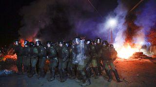 La policía antidisturbios ucraniana se prepara para hacer retroceder a los manifestantes en las afueras de Novi Sarzhany, Ucrania