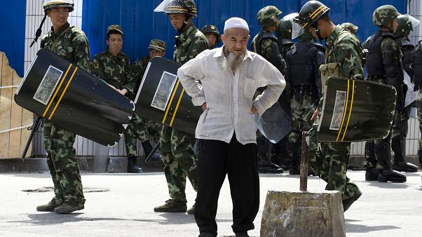 July 8, 2009, file photo, paramilitary police walk past an elderly ethnic minority man in Urumqi, western China's Xinjiang region.