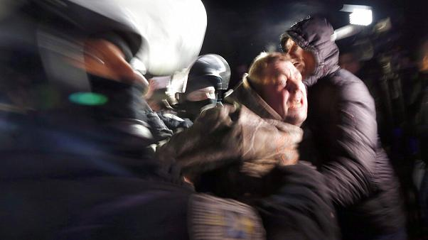 Ukrainian riot police detain a protester, who planned to stop buses carrying passengers evacuated from the Chinese city of Wuhan, outside Novi Sarzhany, Ukraine.