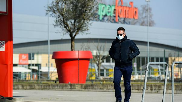 A man wearing a surgical mask walks past a petrol station in Codogno, southeast of Milan, on February 22, 2020