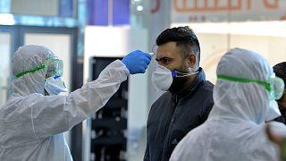 فريق طبي في مطار النجف العراقي يفحص مسافرين وصلوا من إيران، التي وصل منها مسافرون مصابون بالفيروس إلى كل من لبنان وكندا.