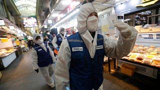 Des agents des services sanitaires dans un marché de Séoul, en,  Corée du Sud, le 24 février