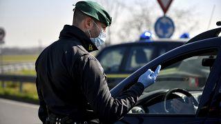 Un policier portant un masque s'entretient avec un conducteur d'un barrage routier à Casalpusterlengo, nord de l'Italie, le lundi 24 février 2020