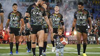 Quaden Bayles, (9), lidera al Indigenous All Stars en el campo con el capitán Joel Thompson antes del partido NRL Indigenous All-Stars vs Maori Kiwis en el CBus Super Stadium