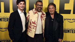 """Jordan Peele, center, executive producer of the Amazon Prime Video series """"Hunters,"""" poses with cast members Logan Lerman, left, and Al Pacino at the premiere of the show."""