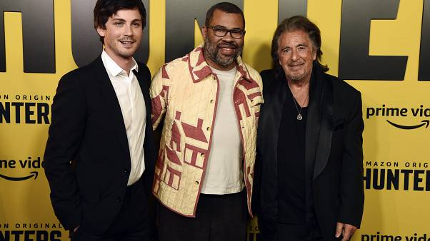 "Jordan Peele, center, executive producer of the Amazon Prime Video series ""Hunters,"" poses with cast members Logan Lerman, left, and Al Pacino at the premiere of the show."