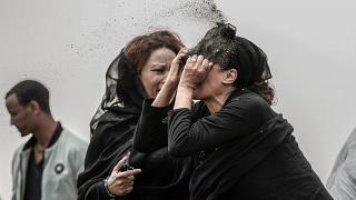 An Ethiopian relative of a crash victim throws dirt in her own face after realising that there is nothing physical left of her loved one.