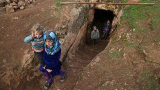 Gyerekek jönnek ki egy menekült család föld alatti búvóhelyéről