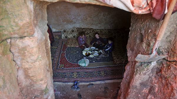 Members of a family of internally displaced Syrians eat together in an underground shelter where several families from Aleppo and Idlib provinces are taking refuge.