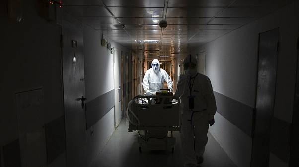 Medical workers move a coronavirus patient at an intensive care unit of the Filatov City Clinical Hospital in Moscow, Russia