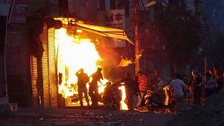 Una tienda arde incendiada por una multitud la incendia durante los violentos disturbios en Nueva Delhi, India.