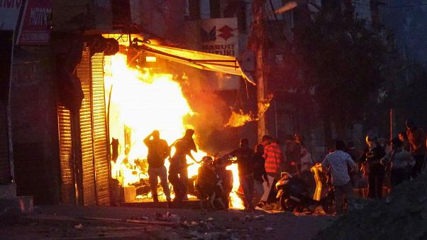 A shop burns as a mob sets it on fire during violent riots in New Delhi, India