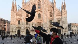A man wearing a protective facemask plays with pigeons in the Piazza del Duomo in central Milan, following security measures taken in northern Italy.