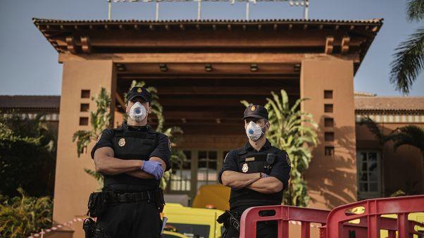 """ضباط شرطة يرتدون أقنعة أمام فندق """"أتش 10 كوستا أديجي بالاس""""، في جزر الكناري بإسبانيا  26/02/2020"""