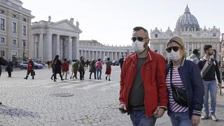 A couple wearing face masks, stroll outside St. Peter's Square, at the Vatican, Thursday, Feb. 27, 2020.