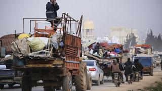 Syrian refugees head northwest through the town of Hazano in Idlib province as the flee renewed fighting Monday, Jan. 27, 2020.