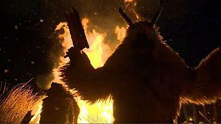 Creature in sheepskin cloak watches coffin representing winter burn