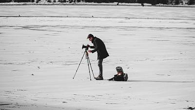 A man filming on a snowy backdrop.
