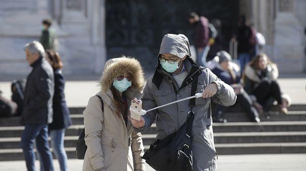 زوجان يرتديان أقنعة الوجه يستعدان لصورة شخصية في ميدان دومو وسط ميلانو بإيطاليا  27/02/2020