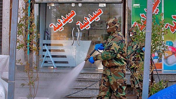 عامل دفاع مدني يستعمل رذاذا مطهرا كإجراء وقائي ضد فيروس كورونا في الأسواق التجارية ووسط المدينة في النجف بالعراق