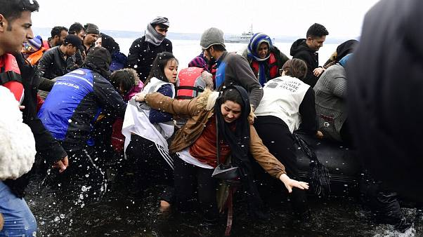 Migrants arrive with a dinghy at the village of Skala Sikaminias, on the Greek island of Lesbos, after crossing the Aegean sea from Turkey, on Friday, Feb. 28