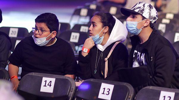 سعوديون يشاهدون مباريات المصارعة الحرة للمحترفين مرتدين اقنعة الوقاية من الفيروس