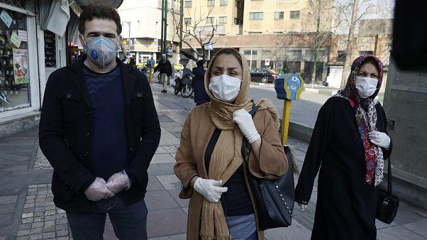 Koronavirüsten korunmak icin maske takan İranlılar