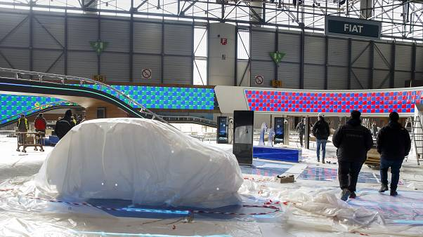 Workers dismantle a booth after that the 90th Geneva International Motor Show is cancelled by Swiss authorities, Friday, Feb. 28, 2020.