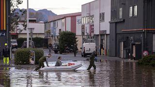 Des habitants traversent une rue inondée avec un canot pneumatique pour inspecter les dégâts dans la ville de Fréjus, en France, lundi 2 décembre 2019.