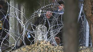 A migrant throws a stone at Greek police and army personnel during clashes near the Kastanies border gate at the Greek-Turkish border, Sunday, March 1, 2020.