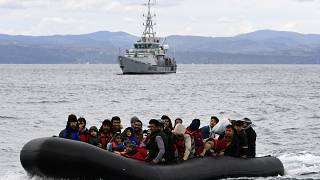 Migrants arrive with a dinghy accompanied by a Frontex vessel at the village of Skala Sikaminias, on the Greek island of Lesbos, after crossing the Aegean sea from Turkey