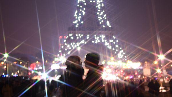 زوجان يتبادلان القبل أمام برج إيفل، خلال احتفالات رأس السنة الجديدة في باريس يوم 2020/01/01.