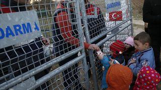 Um trabalhador de ONG distribui leite para crianças na fronteira entre a Turquia e a Grécia