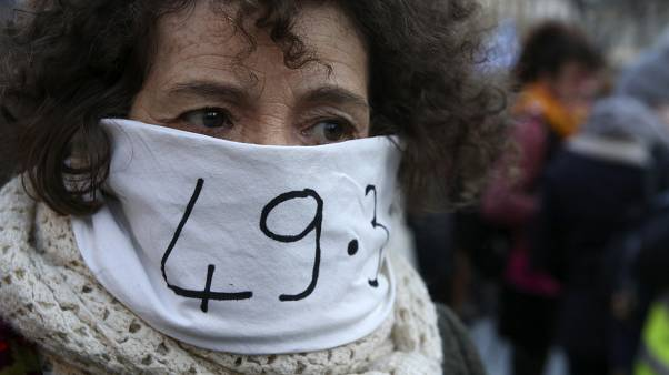 A woman in Marseille protests against the government's use of Article 49.3 of the Constitution to bypass parliament over pension reform.