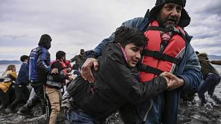 A man helps a young boy to walk after a dinghy with 54 Afghan refugees landed ashore the Greek island of Lesbos