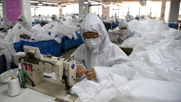 Рабочие на ткацкой фабрике в китайском городе Вэнчжоу шьют костюмы биологической защиты 28 февраля 2020