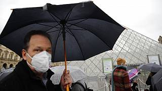 COVID-19 is placing huge demand on masks and gloves, the WHO warned. A tourist wears one outside the Louvre in Paris.