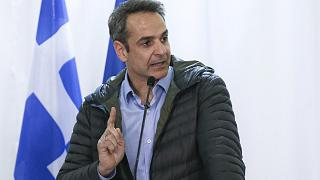 Greek Prime Minister Kyriakos Mitsotakis gestures during a press conference.