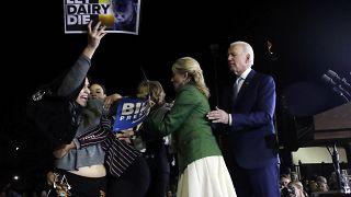 جو بايدن وزوجته جيل لحظة اقتحام متظاهرات للمنصة في التجمع الانتخابي