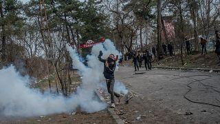 Un migrant renvoie une grenade de gaz lacrymogène à la police grecque à la frontière greco-turque, le 04 mars 2020