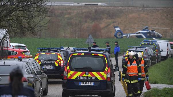 Gendarmes and firefighters gather at the site where a high-speed TGV train locomotive derailed
