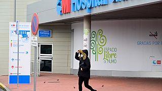 Una mujer con una máscara abandona un hostpital de Madrid