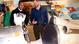 Rennfahrer Hamilton und Prinz Harry betrachten historischen Sportwagen