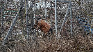 Un migrante se encuentra cerca de la valla fronteriza de la zona de amortiguación de la frontera entre Turquía y Grecia, cerca del paso fronterizo de Pazarkule en Edirne