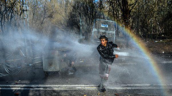Un migrante huye mientras la policía griega utiliza cañones de agua para bloquearlo intentando romper las vallas en la frontera turco-griega de Edirne